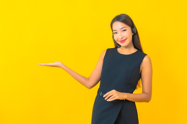 Portrait beautiful young asian business woman with headset call center customer care on yellow background Free Photo
