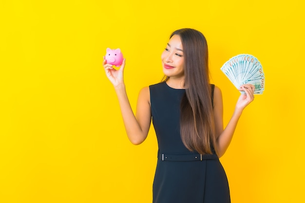 Portrait beautiful young asian business woman with a lot of cash and money on yellow background