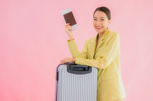Портрет красивой молодой азиатской бизнес-леди с багажной сумкой и паспортом на цвете