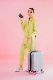 Portrait beautiful young asian business woman with luggage bag and passport on color