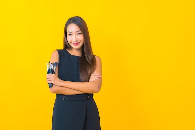노란색 배경에 화장품 브러시 메이크업과 세로 아름 다운 젊은 아시아 비즈니스 여자
