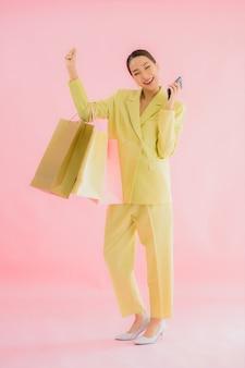 分離された色の買い物袋を持つ美しい若いアジアビジネス女性の肖像画
