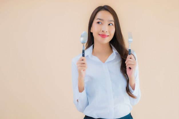 Portrait beautiful young asian business woman with spoon and fork ready to eat