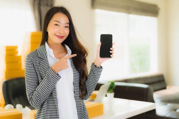 肖像画の美しい若いアジアビジネス女性自宅でラップトップ携帯電話出荷の準備ができて