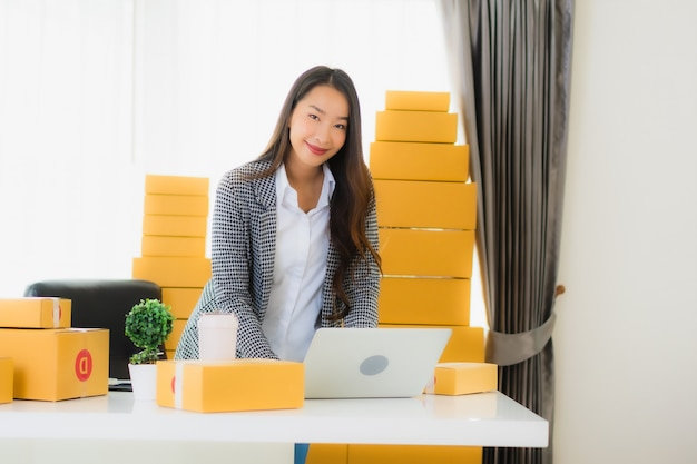 Portrait beautiful young asian business woman work from home with laptop mobile phone with cardboard box ready for shipping