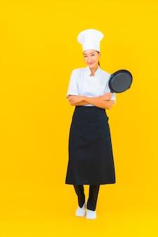 Женщина шеф-повара портрета красивая молодая азиатская с черной кастрюлей на желтом изолированном фоне