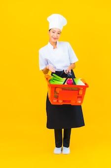 Ritratto bella giovane donna chef asiatica con cesto della spesa dal supermercato su sfondo giallo isolato