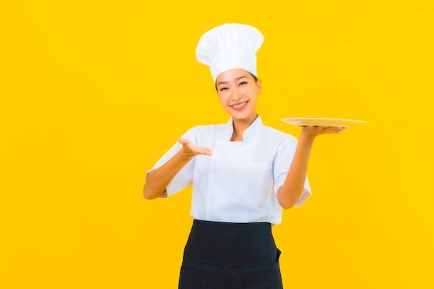 Ritratto bella giovane donna chef asiatica con piastra su sfondo giallo isolato