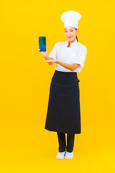 Portrait beautiful young asian chef woman with smart mobile phone on yellow isolated background