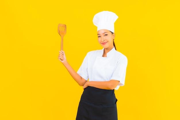 Женщина шеф-повара портрета красивая молодая азиатская с шпателем на желтом изолированном фоне