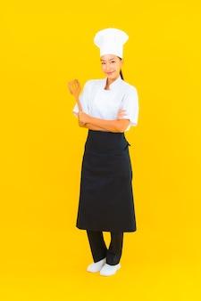 노란색 고립 된 배경에 주걱으로 초상화 아름 다운 젊은 아시아 요리사 여자