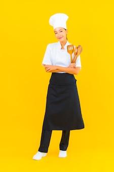 黄色の孤立した背景にへらで美しい若いアジア人シェフの女性の肖像画