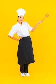 Ritratto bella giovane donna chef asiatica con spatola su sfondo giallo isolato