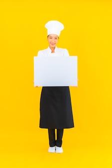 Женщина шеф-повара портрета красивая молодая азиатская с белой пустой афишей на желтом изолированном фоне