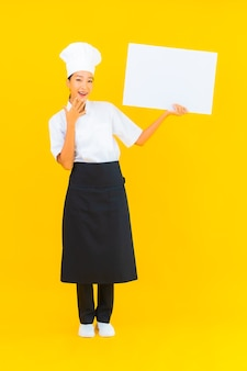 Portrait beautiful young asian chef woman with white empty billboard on yellow isolated background