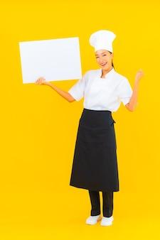 Ritratto bella giovane donna chef asiatica con cartellone vuoto bianco su sfondo giallo isolato