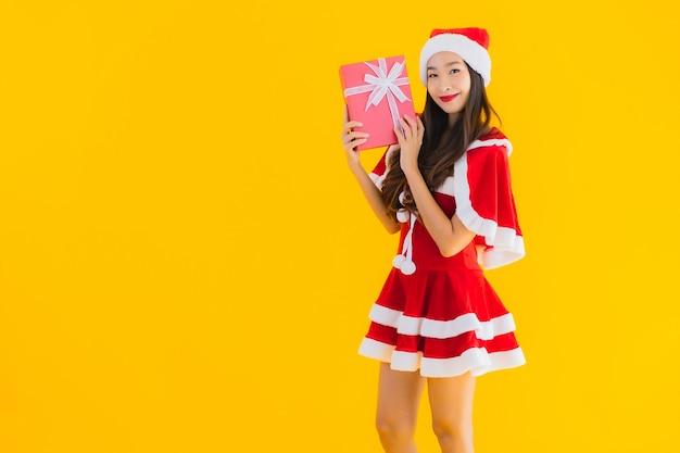 肖像画美しい若いアジアのクリスマスの服と帽子の笑顔は赤いギフトボックスに満足