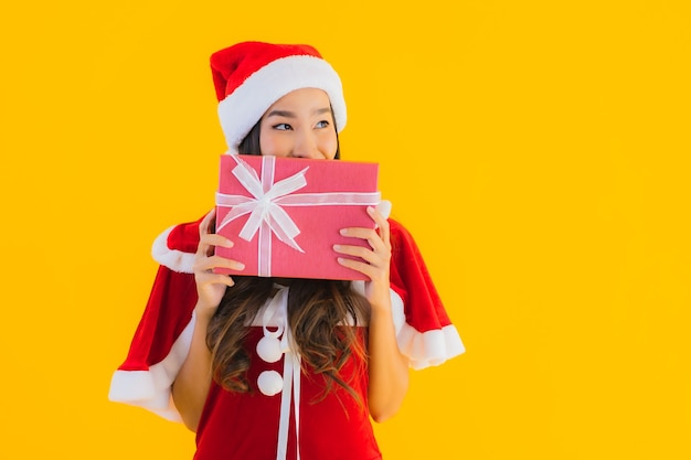 세로 아름 다운 젊은 아시아 크리스마스 옷과 모자는 빨간색 선물 상자와 함께 행복 미소