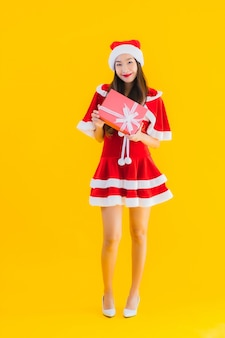 Portrait beautiful young asian christmas clothes and hat smile happy with red gift box