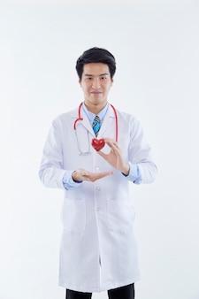 Портрет красивый молодой азиатский доктор мужчина показывает сердце для символа любви на белом изолированном фоне