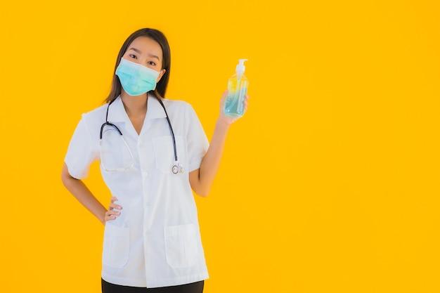 肖像画の美しい若いアジア医師女性はアルコールゲルとマスクを着用します