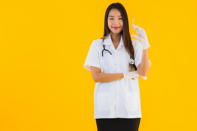 Portrait of beautiful young asian doctor woman wears glove and uses syringe