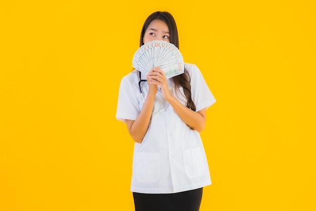 현금 많이 가진 초상화 아름 다운 젊은 아시아 의사 여자