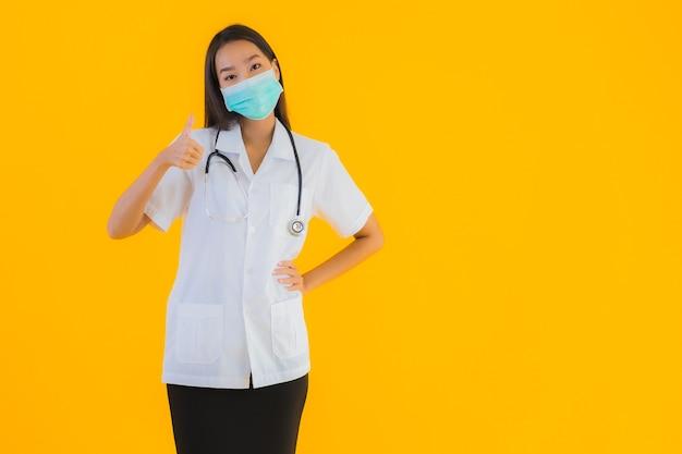 肖像画の保護covid19のマスクを持つ美しい若いアジア医師女性
