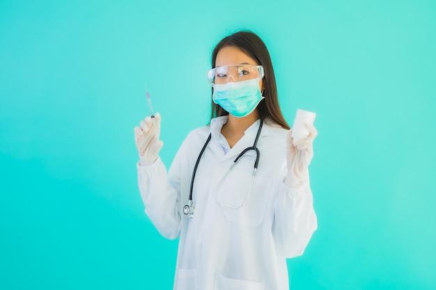 Bella giovane donna asiatica di medico del ritratto con la siringa del vaccino e la bottiglia gettata o della medicina