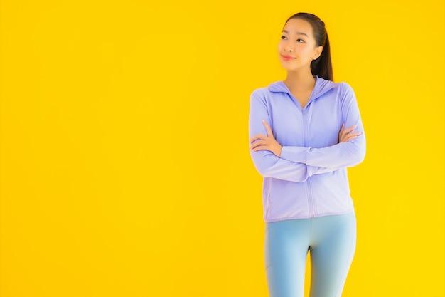 Bella giovane donna asiatica di sport del ritratto pronta per l'esercizio su giallo