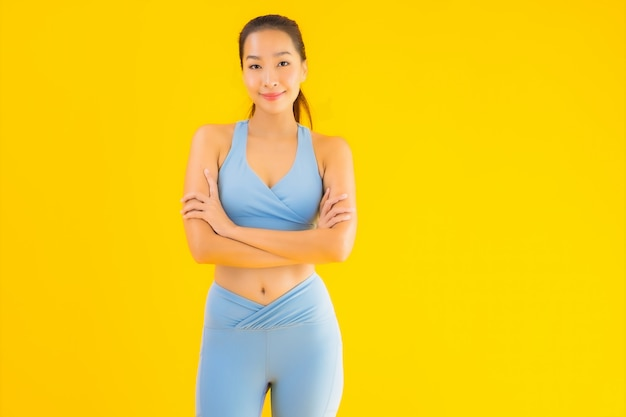 Portrait beautiful young asian sport woman ready for exercise on yellow