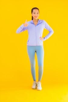 Женщина спорта портрета красивая молодая азиатская готовая для тренировки на желтом цвете