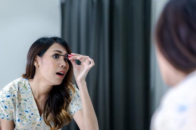 Portrait of beautiful young asian woman applying makeup