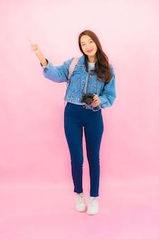 Zaino o bagaglio della bella giovane donna asiatica del ritratto con la macchina fotografica pronta per il viaggio in vacanza sulla parete rosa