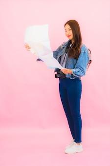 ピンクの壁に休暇で旅行の準備ができてカメラと肖像画の美しい若いアジアの女性のバックパックまたは荷物