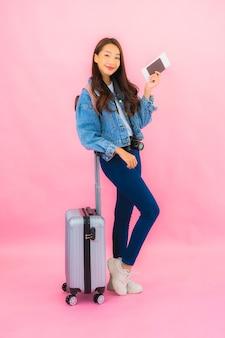 Рюкзак женщины портрета красивый молодой азиатский готовый к путешествию в отпуске на розовой стене