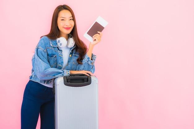 ピンクの壁に休暇で旅行の準備ができて肖像画の美しい若いアジアの女性のバックパック