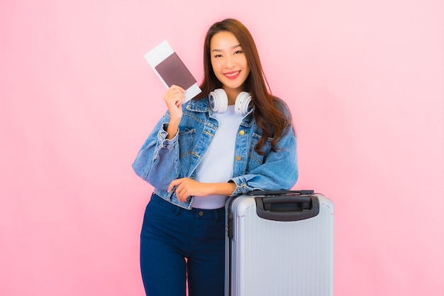 Zaino della bella giovane donna asiatica del ritratto pronto per viaggiare in vacanza sulla parete rosa