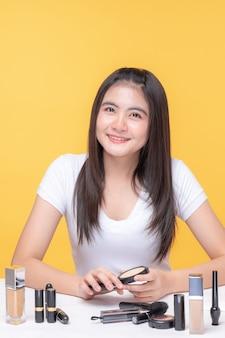 Ritratto di bella giovane donna asiatica bellezza vlogger tenere cosmetici in vendita online
