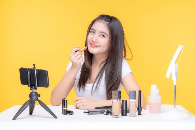 Portrait of beautiful young asian woman beauty vlogger making make-up looking in the camera  blogger recording and streaming video to share on social media