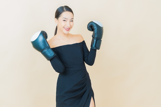 Portrait beautiful young asian woman boxing with glove on yellow