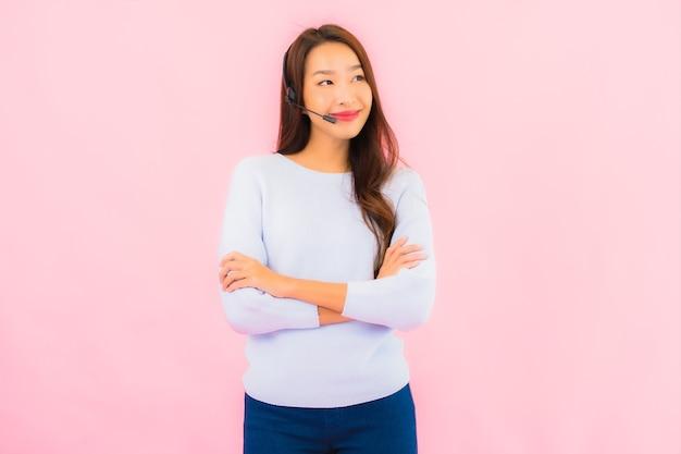 ピンク色の孤立した壁の肖像画美しい若いアジアの女性のコールセンター