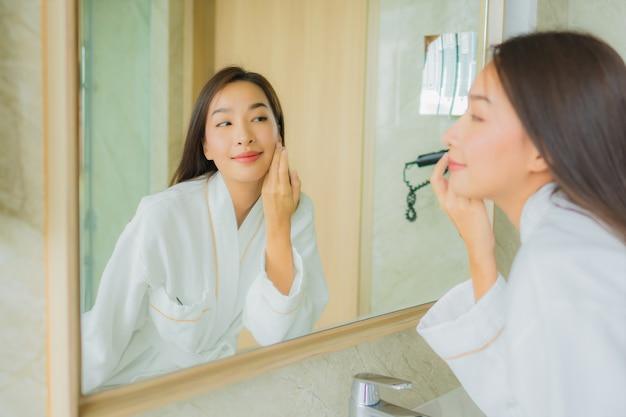 초상화 아름 다운 젊은 아시아 여자 화장실에서 얼굴을 확인
