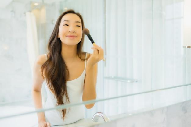 Портрет красивая молодая азиатская женщина проверяет и составляет ее лицо