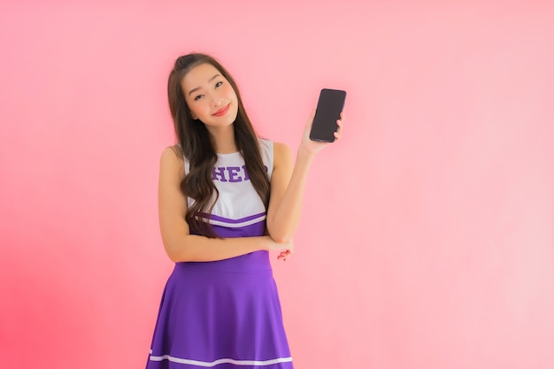 Portrait beautiful young asian woman cheerleader use smart mobile phone