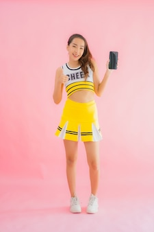 Portrait beautiful young asian woman cheerleader with smart mobile phone