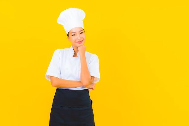 Ritratto bella giovane donna asiatica in chef o cuoco uniforme con cappello su sfondo giallo isolato
