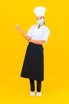黄色の孤立した背景にcovid19またはコロナウイルスを保護するための肖像画美しい若いアジアの女性シェフ着用マスク
