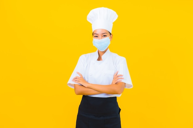 Шеф-повар портрета красивой молодой азиатской женщины носит маску для защиты covid19 или коронавируса на желтом изолированном фоне