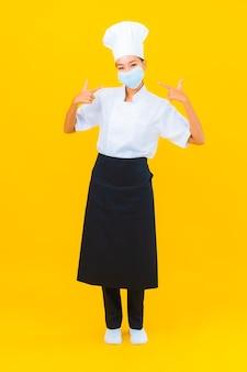 Ritratto bella giovane donna asiatica chef indossa una maschera per proteggere covid19 o coronavirus su sfondo giallo isolato